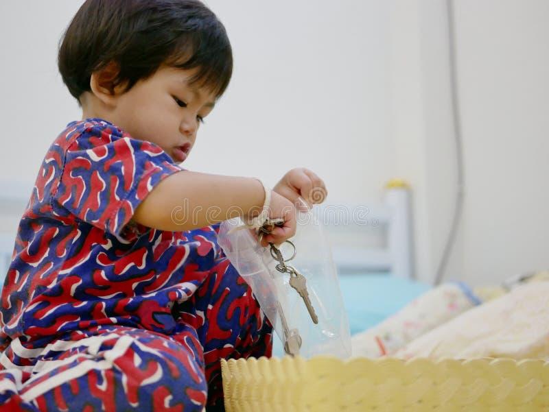 Le petit bébé asiatique essayant de mettre des clés dans une fermeture éclair en plastique mettent en sac seule photos libres de droits