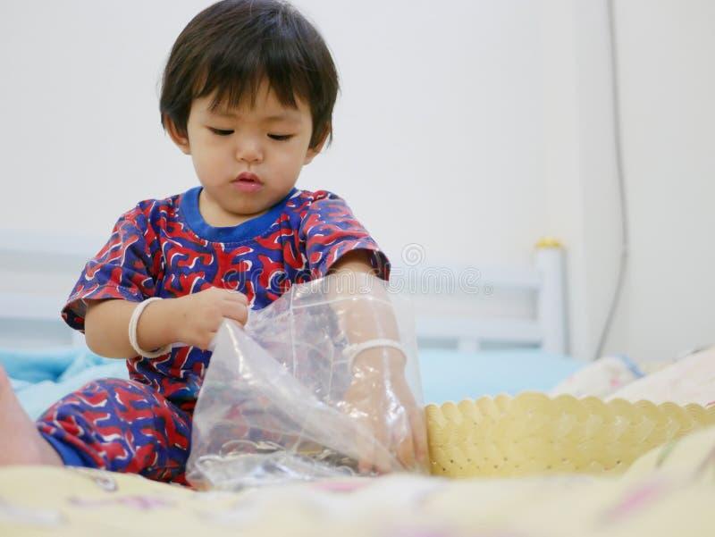 Le petit bébé asiatique essayant de prendre des clés hors d'une fermeture éclair en plastique mettent en sac image stock