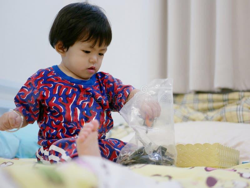 Le petit bébé asiatique essayant de prendre des clés hors d'une fermeture éclair en plastique mettent en sac photographie stock libre de droits