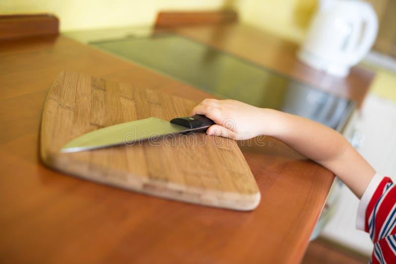 Le petit bébé atteint le couteau de cuisine pointu images libres de droits