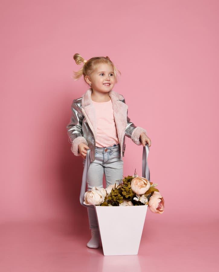 Le petit bébé blond dans la veste rose avec un grand panier de pivoine de fleurs recherche et sourit heureusement photo libre de droits
