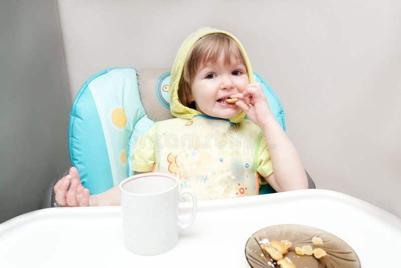 Le petit bébé d'un an mange au highchair photo libre de droits