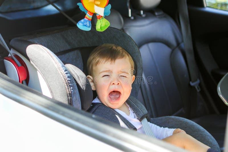 Le petit bébé garçon pleure dans son siège de voiture ne voulant pas se reposer dans lui image stock