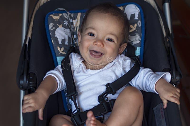 Le petit bébé garçon s'asseyant dans une poussette, préparent pour une promenade dans un pra photo libre de droits