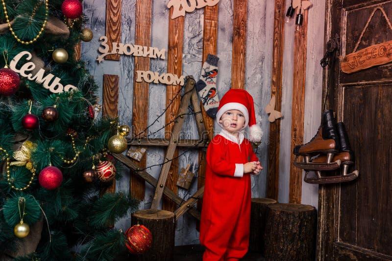 Le petit bébé heureux dans Santa costument près de l'arbre de Noël photos libres de droits