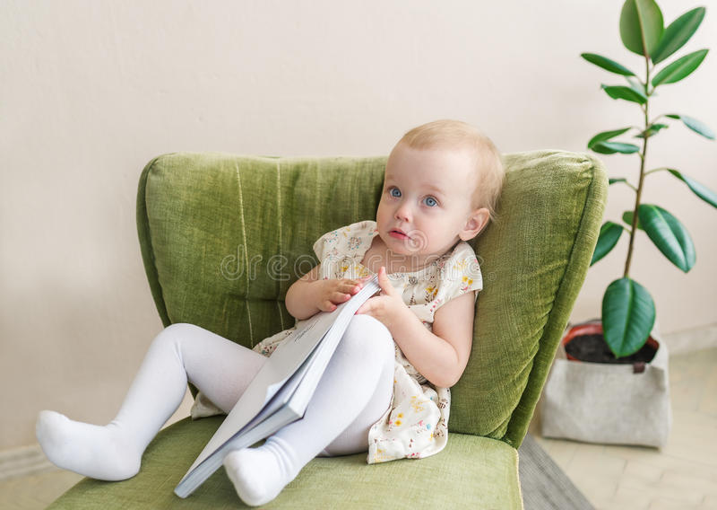 Le petit bébé mignon font le visage drôle, jugeant le livre disponible Enfant s'asseyant sur le fauteuil image libre de droits