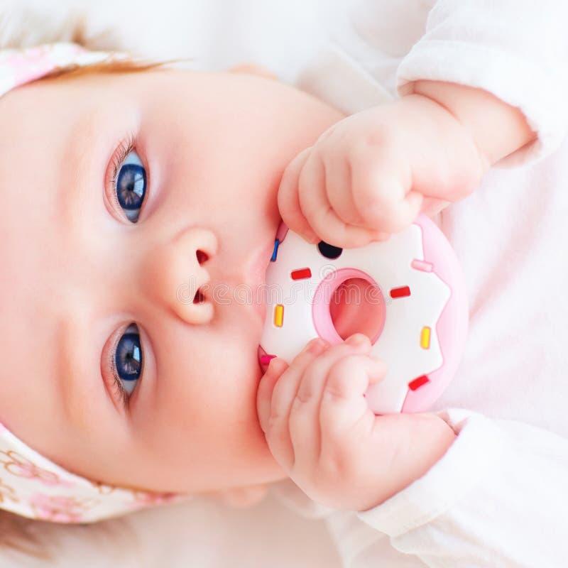 Le petit bébé mignon grignotent un teether de beignet de silicone photo libre de droits