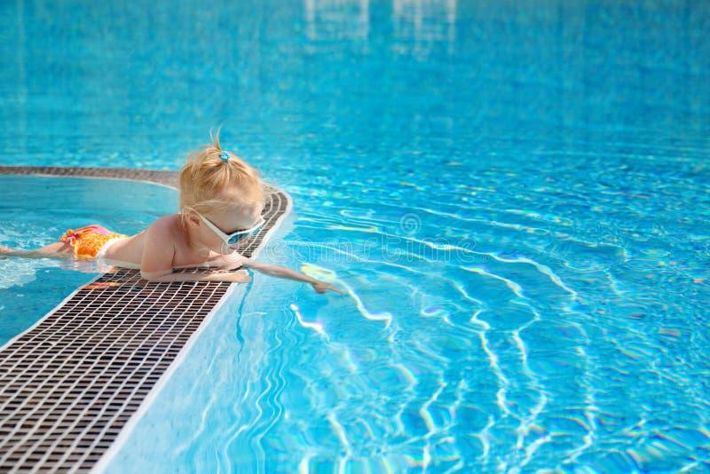 Le petit bébé mignon, se trouvant du côté de la piscine image libre de droits