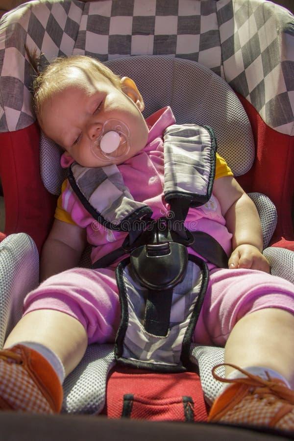 Le petit bébé nouveau-né se repose dans le siège de voiture photo libre de droits