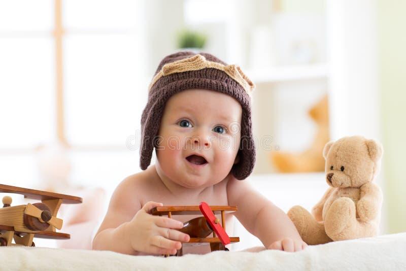 Le petit bébé riant weared le chapeau pilote avec des jouets d'ours d'avion et de nounours photos libres de droits