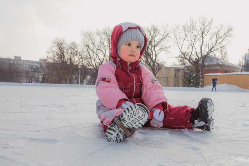 Le petit bébé s'assied sur la glace en hiver image libre de droits