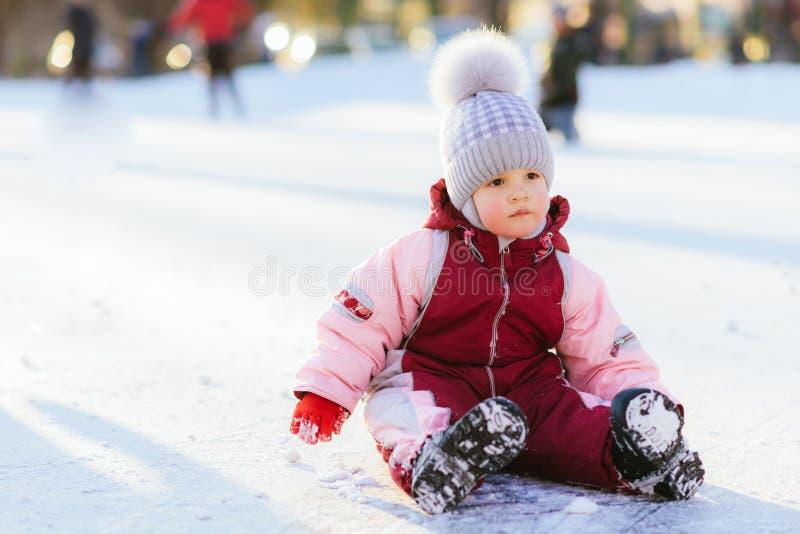 Le petit bébé s'assied sur la neige au coucher du soleil image stock