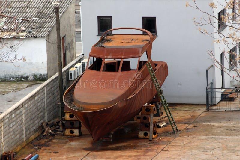 Le petit bateau de mer entièrement rouillé en métal a mis dans l'arrière-cour sur des soutiens importants à reconstituer à la ple photos libres de droits