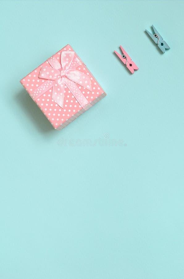 Le petit boîte-cadeau rose et deux chevilles se trouvent sur le fond de texture du papier bleu en pastel de couleur de mode dans  images libres de droits