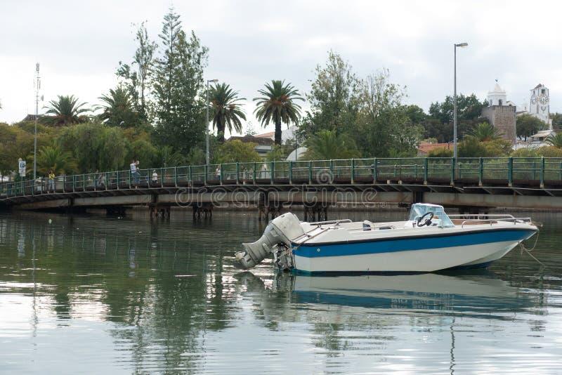 Le petit canot automobile a amarré dans la traversée de la rivière la ville images stock