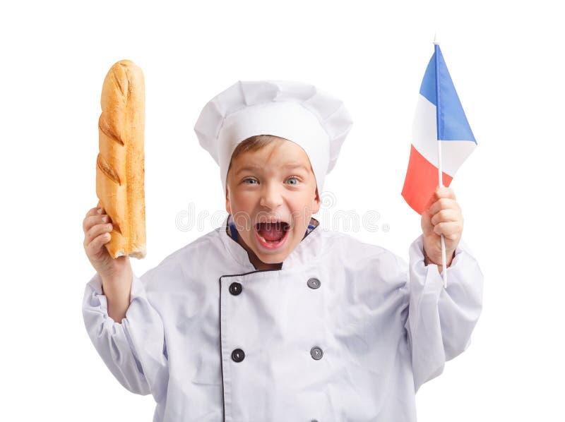Le petit chef avec la baguette et le drapeau français à disposition sur le blanc ont isolé le fond images stock