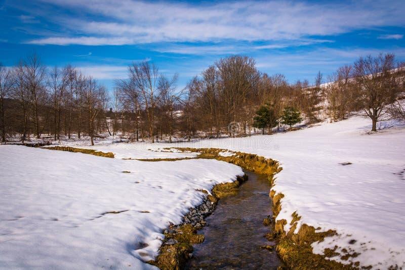 Le petit courant par une neige a couvert le champ de ferme dans Carroll rural photos libres de droits