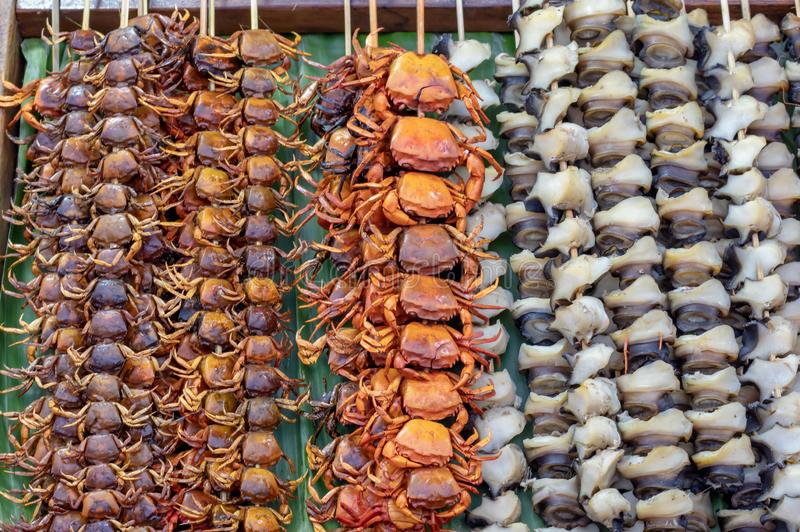Le petit crabe grillé et les coquilles embrochent avec le bambou sur une feuille de banane, ont arrangé dans une rangée photos libres de droits