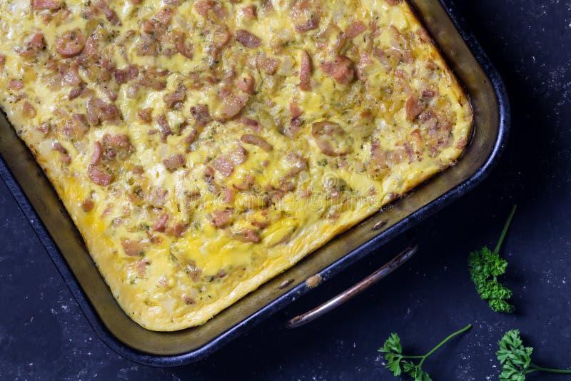 Le petit déjeuner de fromage de lard et de saucisse font cuire au four dans le plateau de four sur le fond noir - tarte savoureus image libre de droits