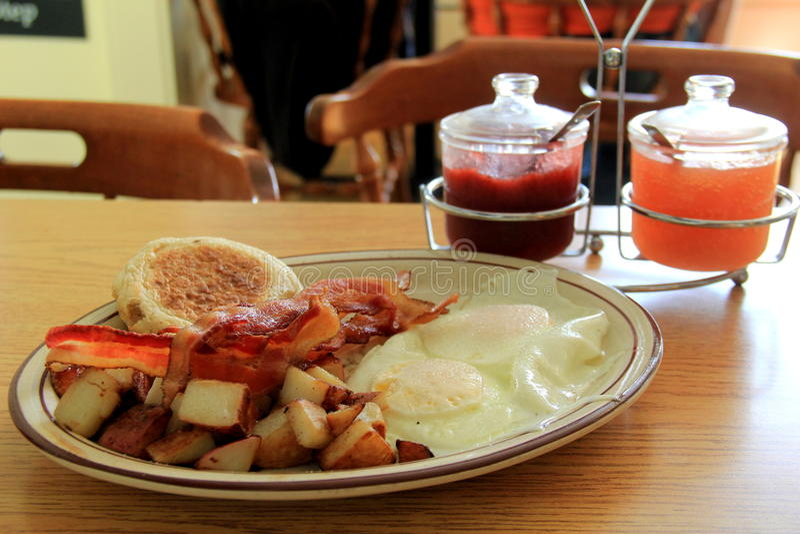 Le petit déjeuner de tentation des oeufs au plat, lard croustillant, maison a fait frire les pommes de terre et le petit pain images libres de droits