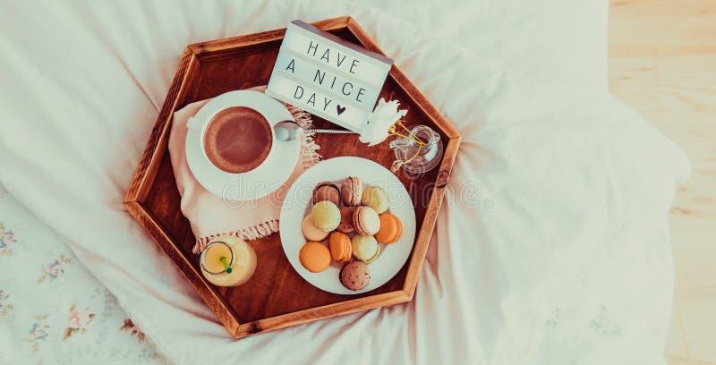 Le petit déjeuner de vue supérieure dans le lit avec ont un texte de beau jour sur la boîte allumée Café, jus, macarons sur le pl images libres de droits