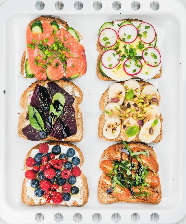 Le petit déjeuner doux et savoureux grille l'assortiment Sandwichs avec le fruit, légumes, oeufs, saumons fumés sur la cuisson bl photographie stock libre de droits