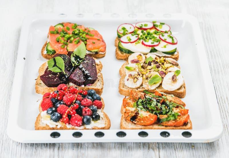 Le petit déjeuner doux et savoureux grille la variété Sandwichs avec le fruit, légumes, oeufs, saumons fumés sur le plateau blanc image libre de droits