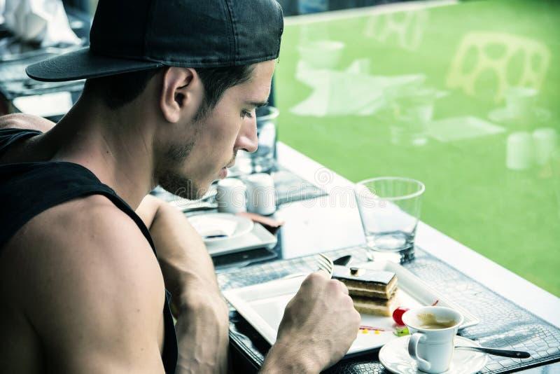 Le petit déjeuner du jeune homme attirant, mangeant le gâteau au wagon-restaurant image stock
