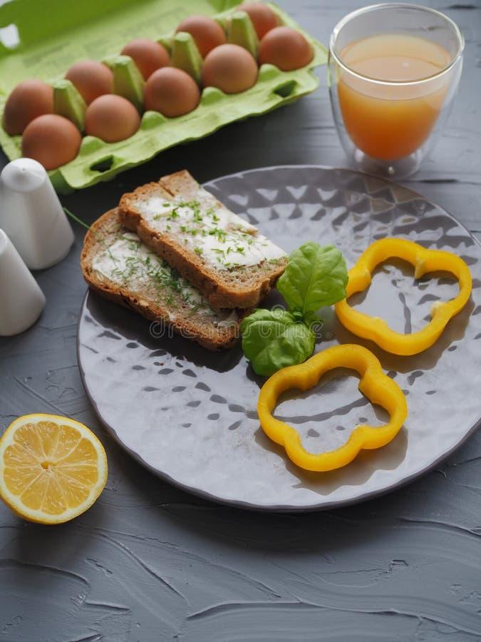 Le petit déjeuner sain avec la maison a fait le pain et les oeufs et le jus d'orange sur le plat gris et l'idéal gris de fond pou photographie stock