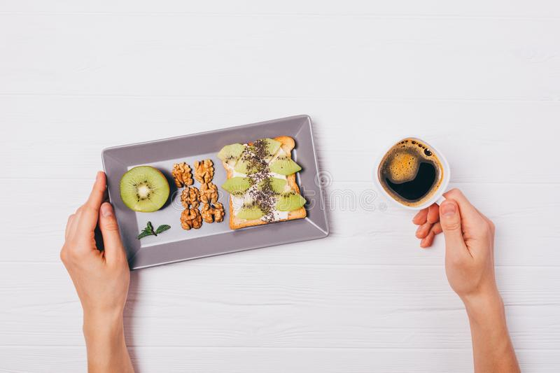 Le petit déjeuner sain du pain grillé doux avec le kiwi, le chia et les noix, appartement s'étendent sur la table en bois blanche photos libres de droits