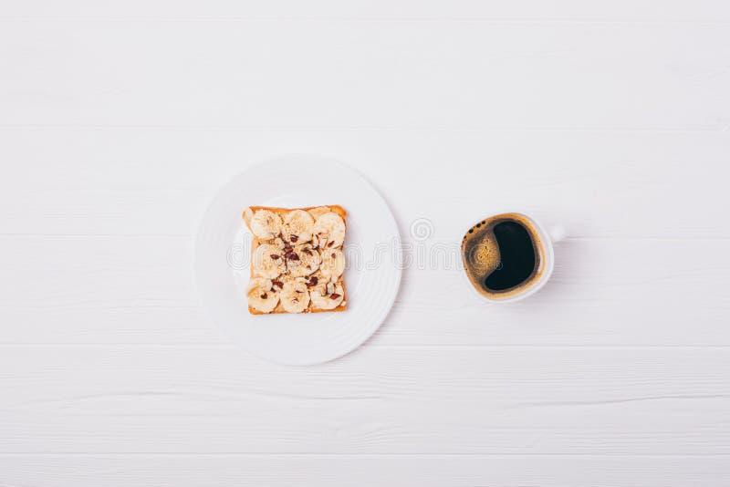 Le petit déjeuner sain du pain grillé doux avec la banane, le beurre d'arachide et les noisettes, appartement s'étendent sur la t photos libres de droits