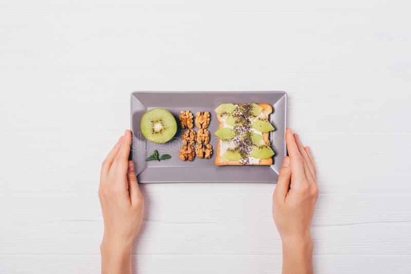 Le petit d?jeuner sain du pain grill? doux avec le kiwi, le chia et les noix, appartement s'?tendent sur la table en bois blanche images stock