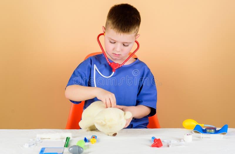 Le petit docteur d'enfant occup? reposent la table avec les outils m?dicaux Examen m?dical st?thoscope r?gl? d'argent de m?decine images libres de droits