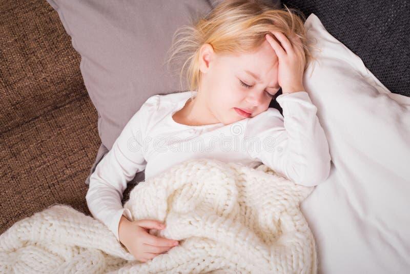 Le petit enfant étant malade et tenant sa main a pressé contre son front image stock