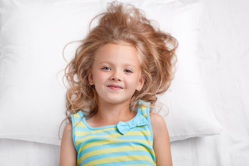 Le petit enfant attirant avec l'aspect agréable, les yeux bleus et la peau saine regarde l'appareil-photo, pose dans le lit à la  images libres de droits