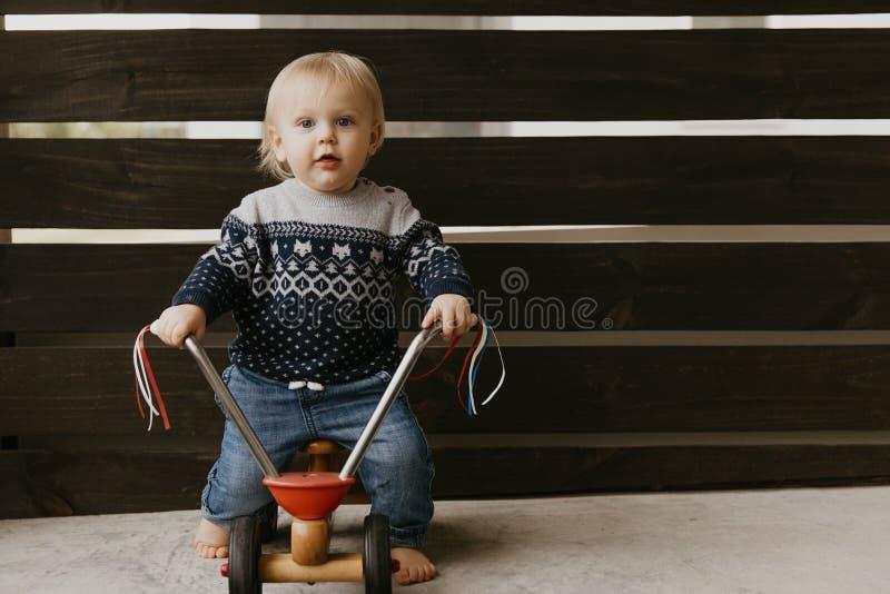Le petit enfant blond mignon adorable précieux de garçon d'enfant en bas âge de bébé jouant dehors sur Toy Bicycle Scooter Mobile photo stock
