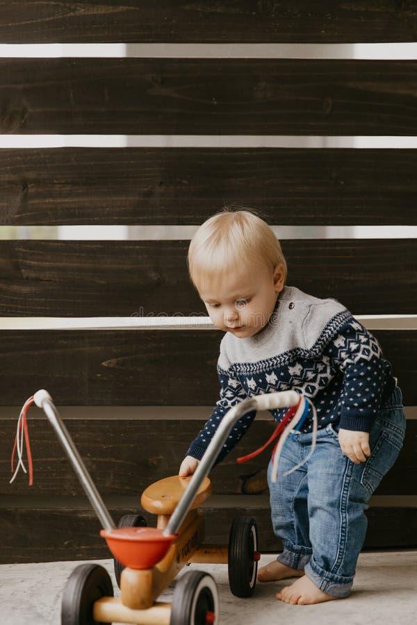 Le petit enfant blond mignon adorable précieux de garçon d'enfant en bas âge de bébé jouant dehors sur Toy Bicycle Scooter Mobile image stock