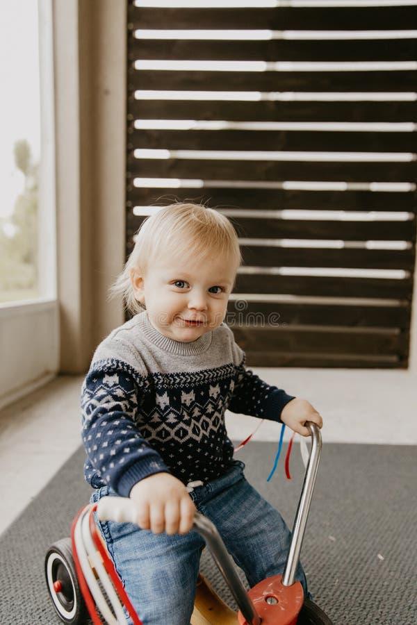 Le petit enfant blond mignon adorable précieux de garçon d'enfant en bas âge de bébé jouant dehors sur Toy Bicycle Scooter Mobile images libres de droits