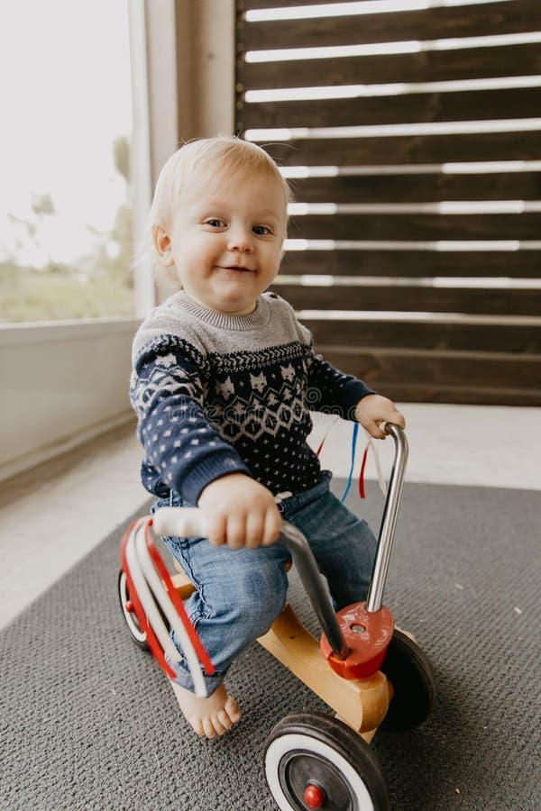 Le petit enfant blond mignon adorable précieux de garçon d'enfant en bas âge de bébé jouant dehors sur Toy Bicycle Scooter Mobile photo libre de droits