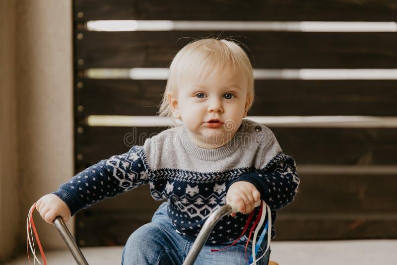 Le petit enfant blond mignon adorable précieux de garçon d'enfant en bas âge de bébé jouant dehors sur Toy Bicycle Scooter Mobile image libre de droits