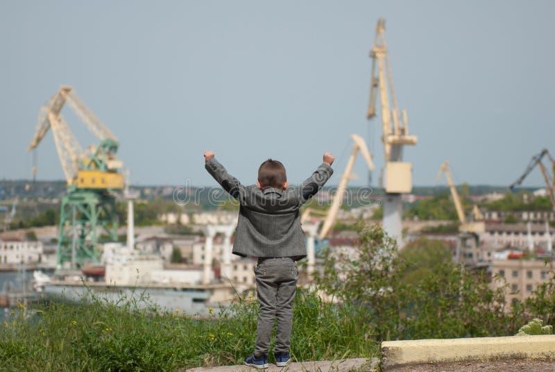 Le petit enfant dans la veste a soulevé ses mains à l'arrière-plan du port maritime photo stock