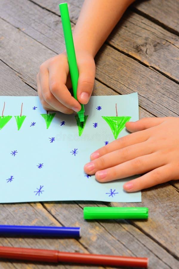 Le petit enfant dessine des arbres et des flocons de neige de Noël sur le papier images libres de droits