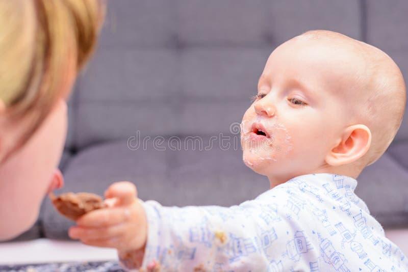 Le petit enfant donne à un goût du gâteau votre mère image stock