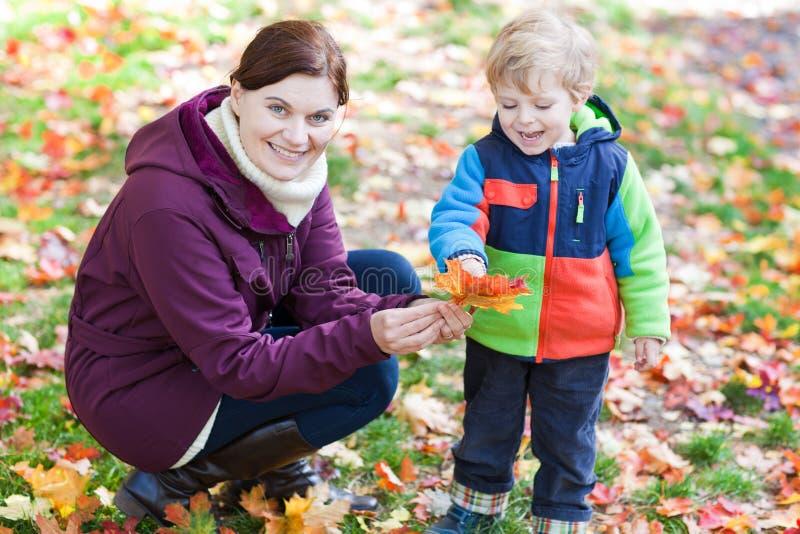 Le petit enfant en bas âge et la jeune mère en automne stationnent photo libre de droits