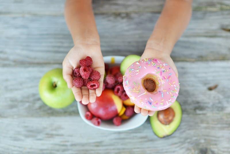 Le petit enfant essayant de décider de manger la framboise fraîche porte des fruits avec les vitamines ou le beignet délicieux ma image libre de droits