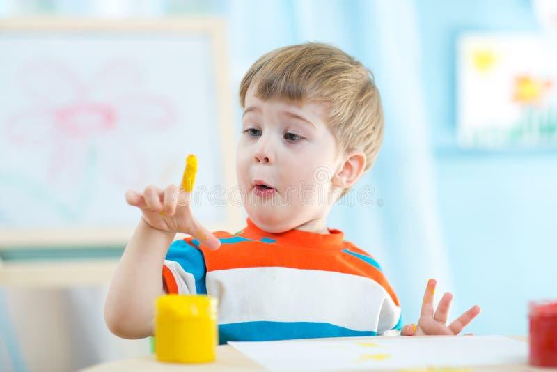Le petit enfant est heureux de peindre le tableau tout en se reposant à son bureau photos libres de droits