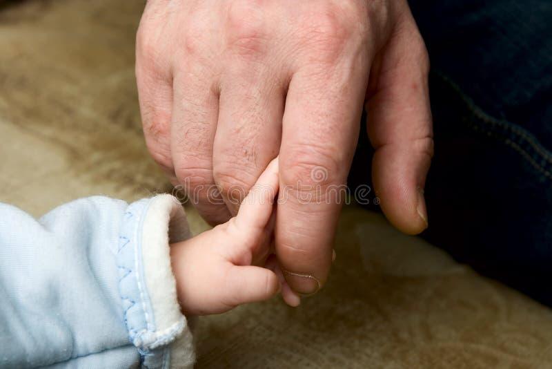 Le petit enfant gardant pour un doigt du père photo libre de droits