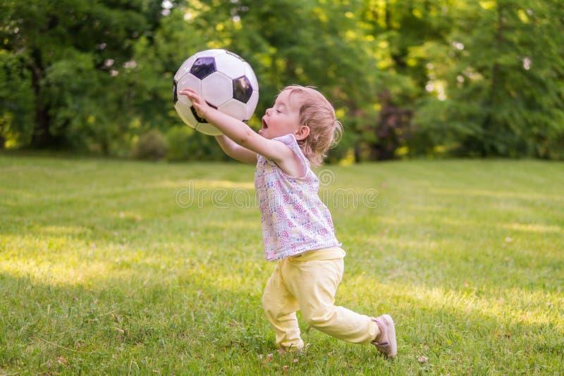 Le petit enfant joue avec la boule du football en parc images libres de droits