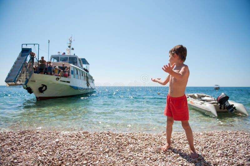 Le petit enfant mignon dans des shorts rouges rencontre le bateau de arrivée sur la plage d'île d'été images stock