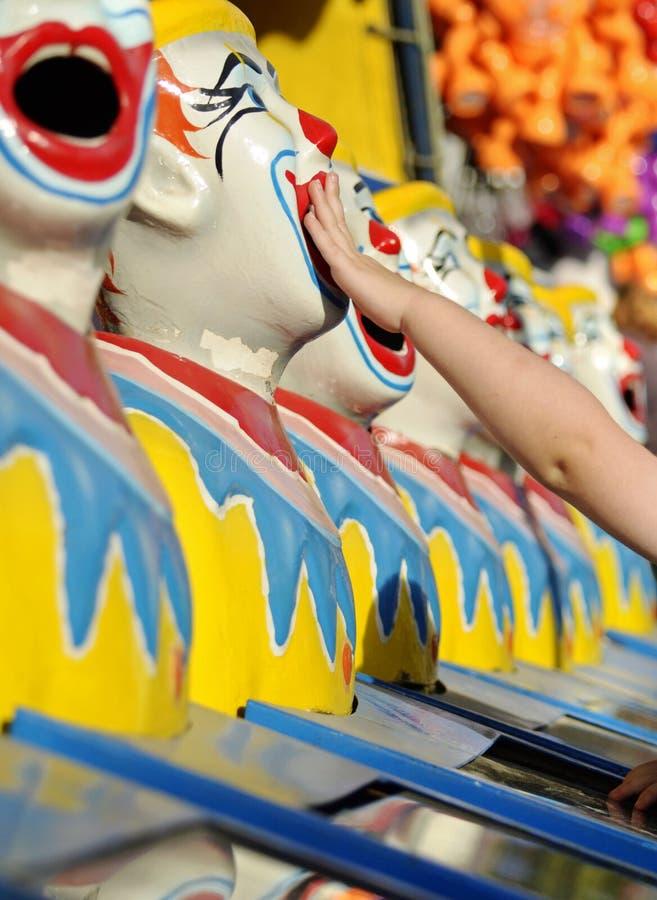 Le petit enfant plaçant la boule dans la bouche de rire fait le clown jeu à la foire d'amusement photo libre de droits